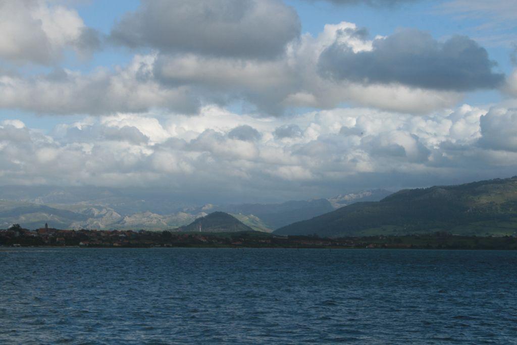 'Algodon sobre la bahía'. Tarde lluviosa en la bahía de Santander. Al fondo las montañas tienen una ténue luz que atraviesa las gruesas nubes blancas y negras. Autora: Raquel Palencia