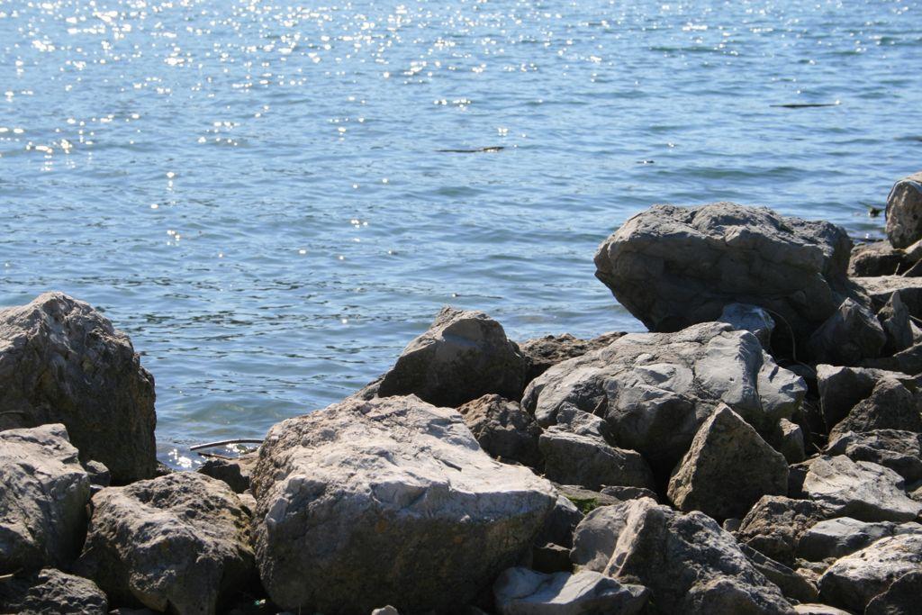 'Brillante Tranquilidad'. Destellos de luz en la ría de Suances haciendo contraste con las rocas. Autora: Raquel Palencia