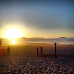 'Aprovechando los últimos rayos de sol'. Playa de Somo, con el sol poniéndose al atardecer tras un día caluroso de playa. Y unos chicos aprovechando los últimos minutos de sol. Autora: Raquel Pellón