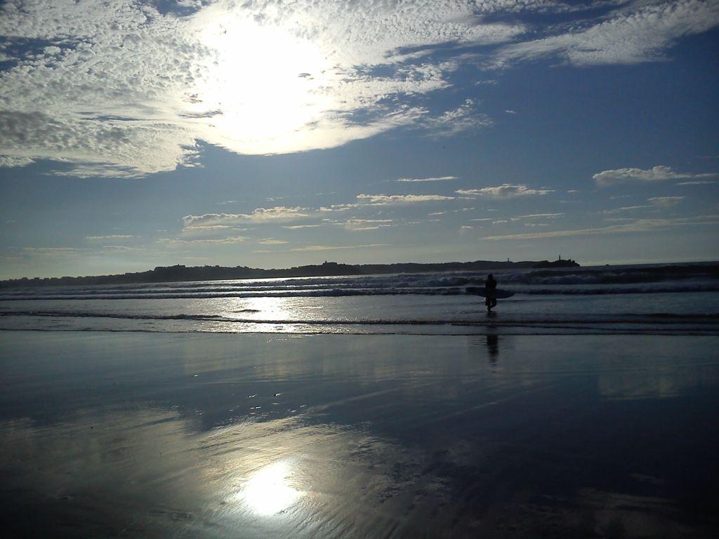 'Tarde ideal del baño'. Foto tomada desde Loredo, con nubes reflejadas en el agua, junto con un surfista a la derecha. Autora: Raquel Pellón
