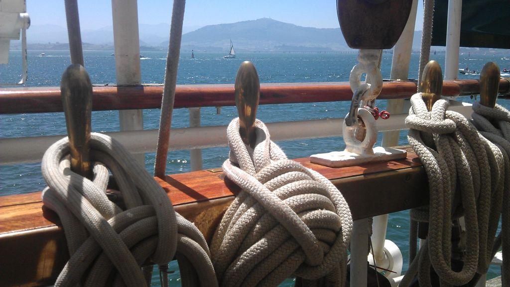'A los pies de la peña'. Aprovechando la visita de Elcano se me ocurrió hacer esta foto cuando estaba mirando desde el propio barco la bahía. Pensé que resultaba bonito ver entre todos los aparejos del barco la silueta de la montaña que siempre está pendiente de nuestra bahía. Es el faro y la vigía de la bahía. Autor: Tomás Amparán