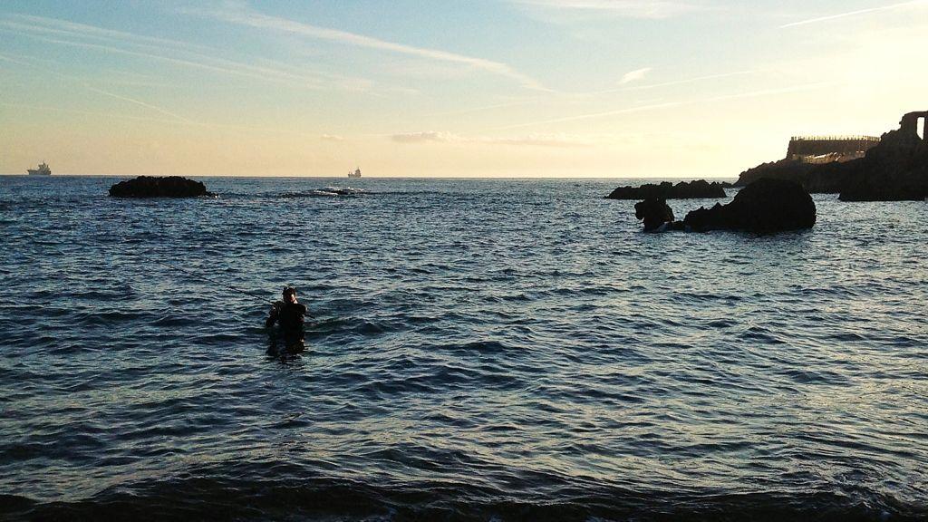 pescador con neopreno saliendo del agua en la playa del camello en santander