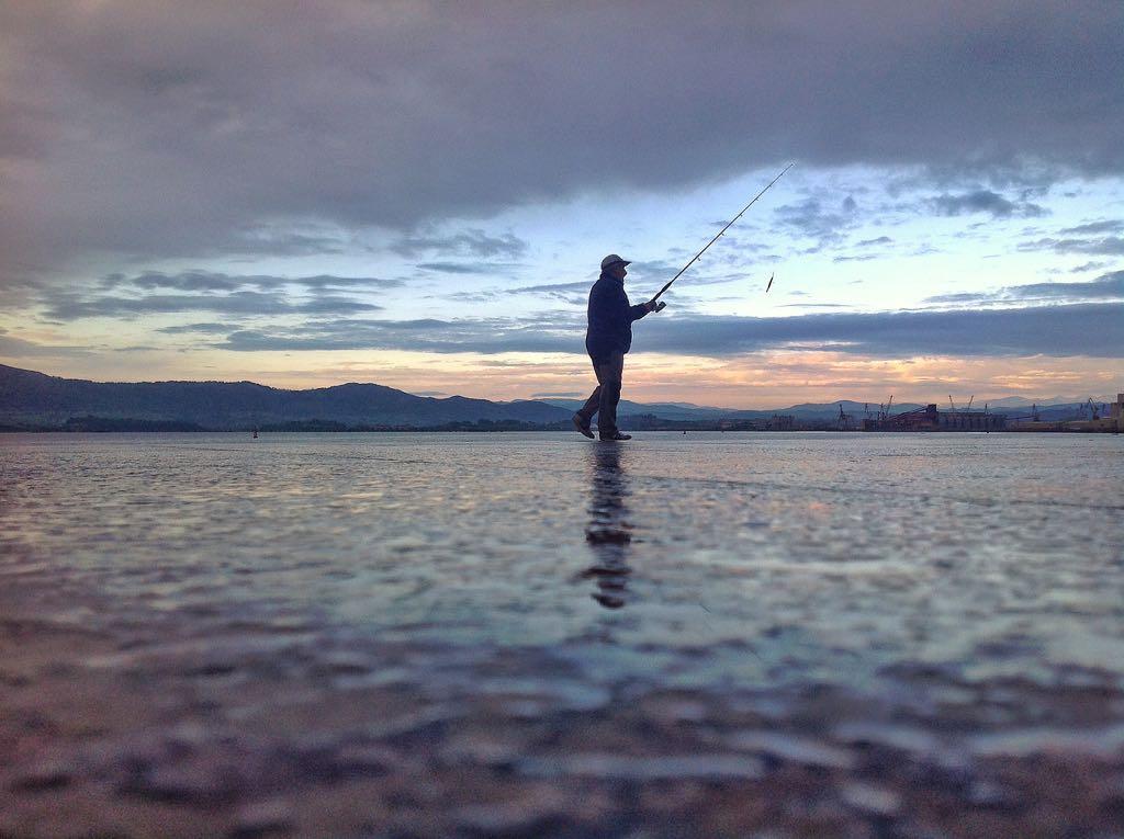 pescador-camina-bahia-santander