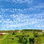 Césped, rocas, cielo y nubes de algodón