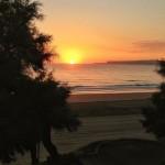 El sol sale del agua en un amanecer de postal