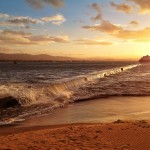 La marea se come el espigón de bikinis en un atardecer dorado